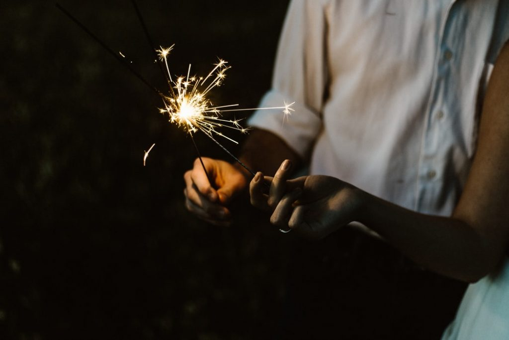 Hand holding lit sparkler at night.
