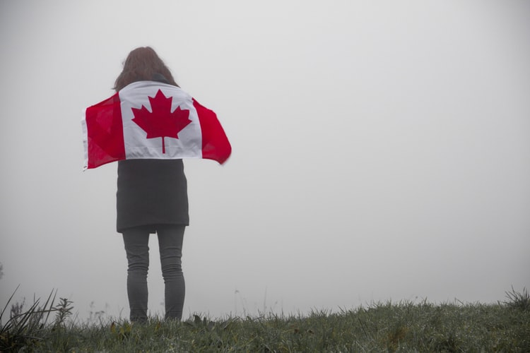 Girl with Canada flag around her shoulders.