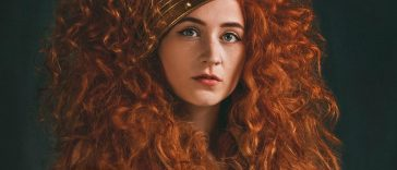 Book cover of My Confessional by Janet Devlin which sees her naked with her long auburn curly hair flowing over her shoulders with a crown on her head.