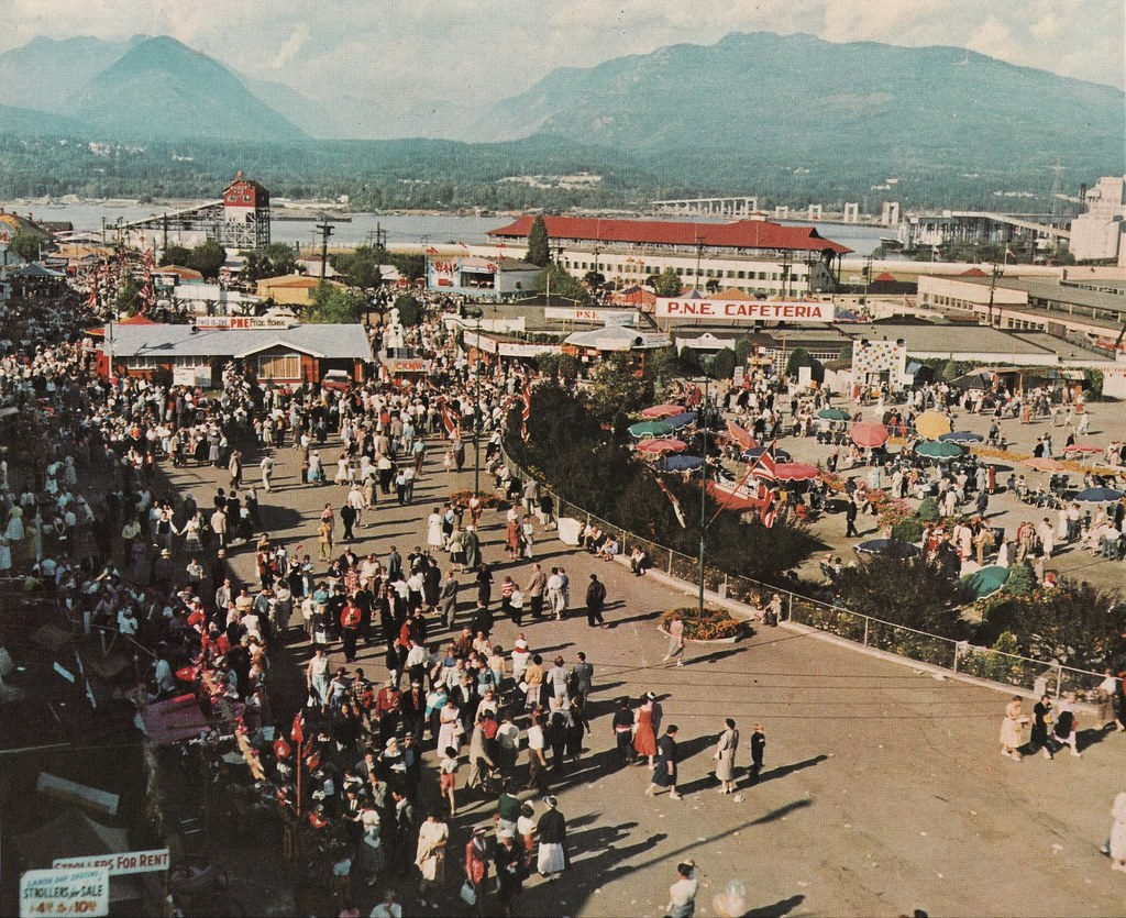 Wide shot of people walking through the PNE in 1957.