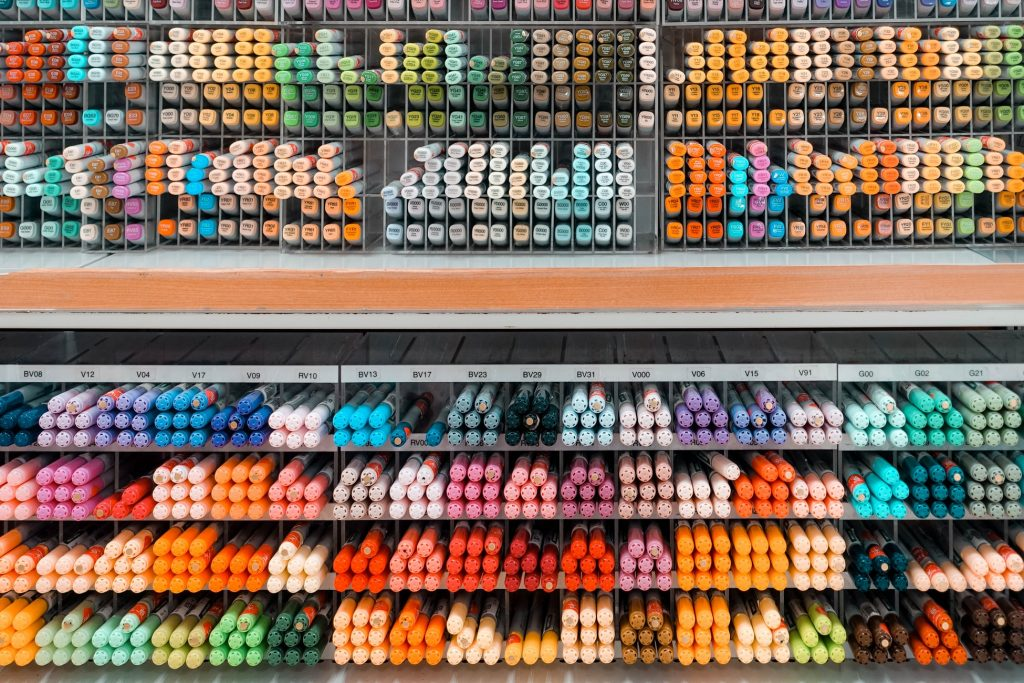 Pens organized by colour at a store.
