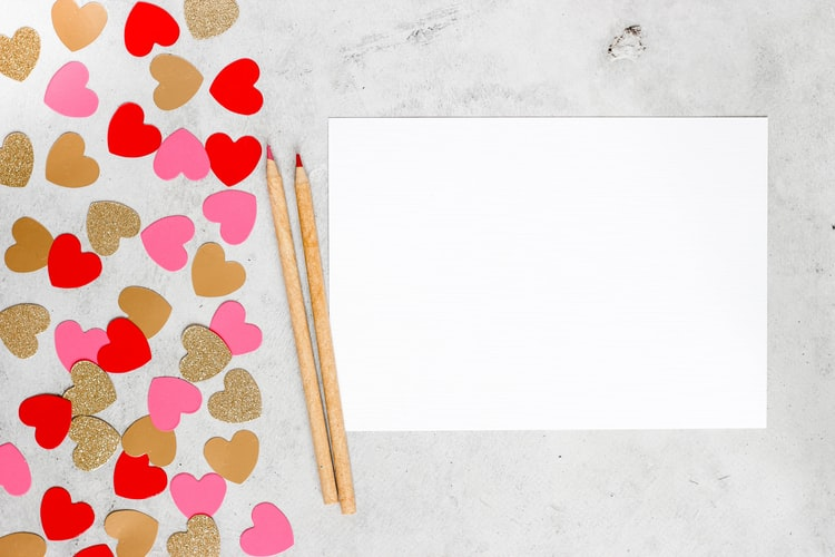Paper hearts next to two pencils and a blank sheet of paper.