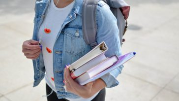 Student wearing headphones and holding books
