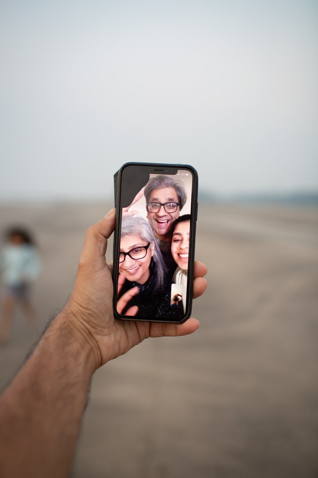 Person holding a phone that shows a family on Facetime