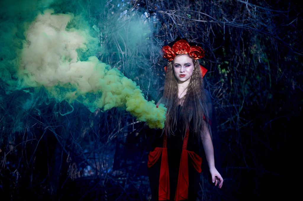 Girl in red Halloween costume standing among smoke in forest