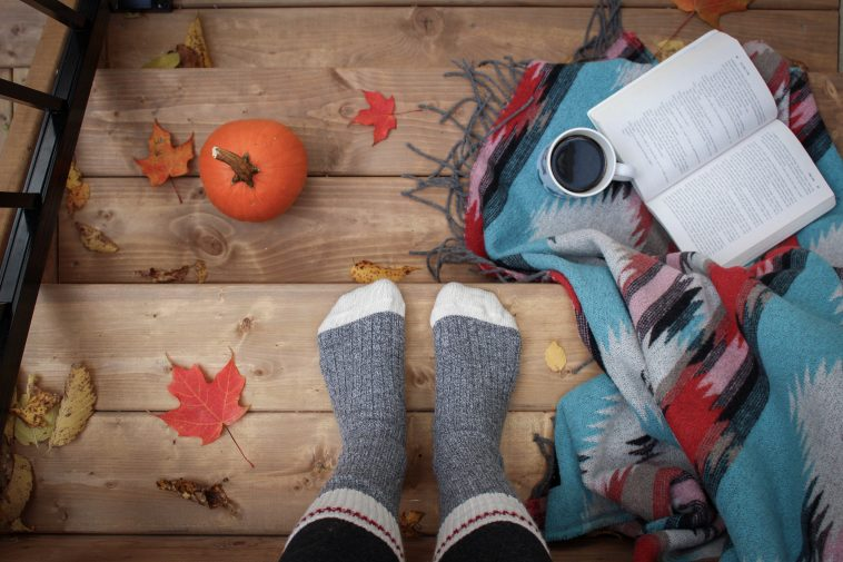 someone sitting on stairs, wearing grey socks, and has blanket with a cup of coffee and a book on right