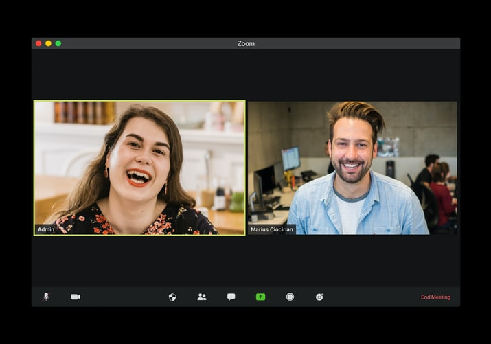 Two people smiling on a virtual Zoom call.