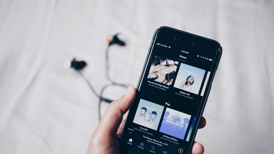 Hand holding phone showing playlists.