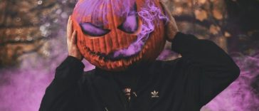 Man surrounded by purple smoke with pumpkin on his head.